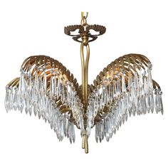 Gilt Brass Palm Chandelier  Portugal  c. 1940s  Fine chandelier of gilt brass, having three palm fronds embellished with hanging crystal pendulum prisms, surmounted by a ribbon, and finished with a chased bowl and tassels.