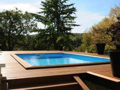 Piscine de forme carrée surélevée grâce à une terrasse en lame de bois ciré. Un petit escalier en bois permet d'accéder à la piscine.