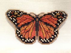 "This beautiful butterfly is stitched with various shades of orange, gray, and black. It is embellished with orange, cream, and rainbow colored glass beads. 3.5""w x 1.75h $12"