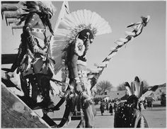 """Three Indians in headdress in foreground watching tourists, """"Dance, San Ildefonso Pueblo, New Mexico, 1942."""" by The U.S. National Archives, via Flickr"""