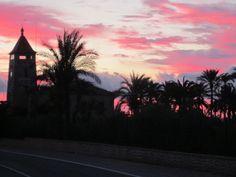 Torre decimonónica de San Matías y huerto tradicional de palmeras, con amanecer rojizo a finales de Octubre, en la pedanía rural ilicitana de Asprillas (ELX)