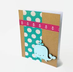 4.25 USD  This adorable whale is ready to make you smile! The card features a whale on a kraft paper background. Blue and white polka dot washi tape and pink and white anchor print washi tape add bright pops of color! This card is perfect to celebrate a new baby or to give as a birthday card. You can also send it just to cheer up a friend! This card is handmade with love and care by Paper Ocean Design Co. It measures 5.5 inches by 4.25 inches. The base is white cardstock. The card is blank…