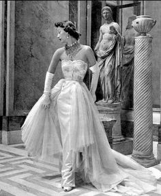 Sophie Malgat with sculpture at Musée Jacquemart-André, Paris, Photograph by Pottier. Margat wears a gorgeous narrow white satin gown, the bodice embroidered with pearls and brilliants. Layers of white tulle form a train over the skirt. Vintage Fashion 1950s, Vintage Gowns, Vintage Couture, Vintage Bridal, Vintage Glamour, Vintage Outfits, Vintage Wedding Photos, Vintage Dior, Vintage Hats