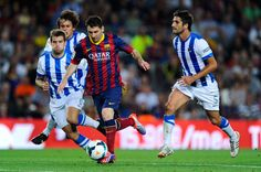 Lionel Messi of FC Barcelona duels for the ball among Real Sociedad de Futbol players during the La Liga match between FC Barcelona and Real Sociedad de Futbol at Camp Nou on September 24, 2013 in Barcelona, Catalonia.