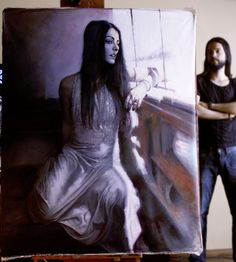 Contemporary figurative artist Renato Guedes stands beside one of his female paintings in his art studio #workspace #atelier.