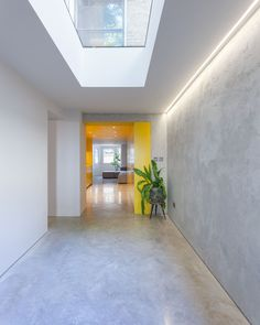 Hidden lighting, a skylight and a yellow kitchen ensure that this modern basement feels bright and open. #Skylight #Lighting #YellowKitchen