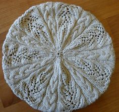 Cascade Beret is a cable and lace beret knit on two circular needles and inspired by the shapes and movement of water as it tumbles over rocks.