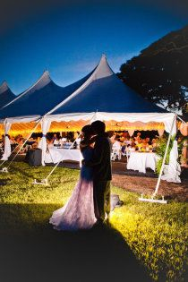 Bride and Groom in front of wedding reception tent on Jekyll Island next to beach.