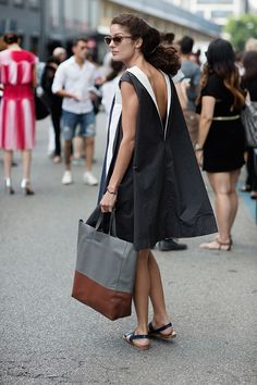 Love how this woman in Milan dresses down a sculpted, backless dress with a big leather bag and flat sandals. Gorgeous cat-eye sunglasses, too! #Italianstyle