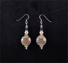 Lovely earrings. Purple and beige lampwork glass bead earrings.   *Beads: Lampwork and glass beads   *Earwires: Sterling silver   *All other metal is silver plated.   *Length: 1.6 inches (from the bottom of the ear hook)   *Width: 0.7 inches (at the widest part)   *Handcrafted in Fayetteville, Arkansas