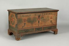 """Realized Price: $140,400   Lehigh County, Pennsylvania painted dower chest, late 18th c., the cartouche inscribed """"Hanna Eister 1790 Gebert Diese Kist."""", above 2 stylized green sponge decorated hearts centering on an orange and black pinwheel and tulip tree flanked by similar stars and tulips and heart corners on an ochre and red stippled ground, the ends with bold red and ivory stars, above 3 green sponge decorated drawers retaining original hardware supported by spurred straight bracket feet,"""