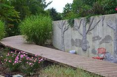 How I disguised an ugly concrete retaining wall with tile, mortar and carved vertical concrete.