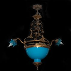 """DESCRIPTION: Chandelier features a gilded bronze frame decorated with floral designs and a opaline glass center painted in a light blue hue. Two arms stretch to the sides finished with crystal blue shades surrounding light fixtures. CIRCA: late 19th Ct. ORIGIN: France DIMENSIONS: H: 36"""" L: 32"""""""