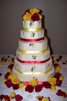 Octagon maroon and gold ribbon wedding cake with fresh roses and music notes