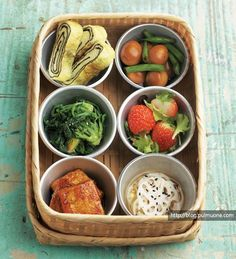 Korean style spring lunchbox - egg rolls, simmered quails eggs, spinach salad, strawberry salad, spicy tofu,  pickled lotus root