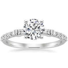 Bar-set diamond baguettes and round diamond accents frame the sparkling center gem in this chic ring that embodies an elegant combination of modern and vintage design.
