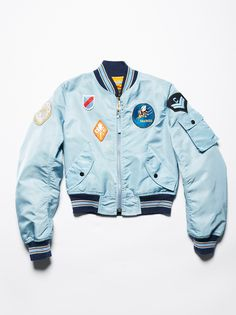 Vintage Flight Bomber Jacket | Light blue bomber jacket from the 1990s with allover sewn-on patches and contrast striped ribbed detailing. Two front pockets and a zipper closure.