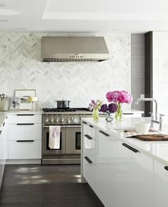 Ultra modern, crisp and clean lined... white on white used to the full effect in this kitchen.  The basket weave marble backsplash gives great yet subtle impact