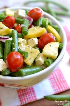 Fresh Green Bean Salad with yellow squash, grape tomatoes, red onions, and feta cheese in a light lemon vinaigrette dressing