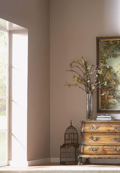 "Because they're located on the opposite ends of the color wheel, the mauve walls in Glidden's ""Midday Mocha"" complement the light greens of this hallway's central painting. 