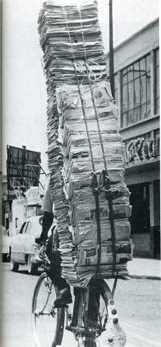 human transport: newspaper pile on bicycle (via firsttimeuser.tumblr 17401188510)