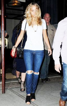 Jennifer Lawrence wears a white t-shirt, distressed jeans, and a Diane von Furstenberg bucket bag
