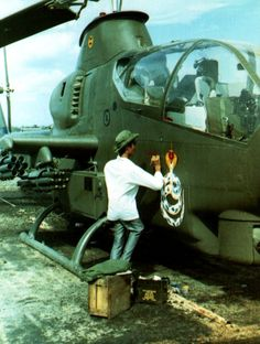 A cobra being painted on the side of a Cobra Attack Copter by a local Vietnamese artist.~ Vietnam War