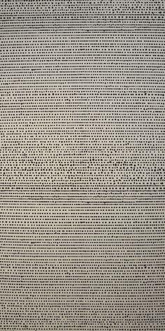 Grafiskt limtryckta små prickar i oregelbundna former som ser ut som färgdroppar. Dimensionen på mönstret gör att tapeten upplevs enfärgad när den sitter på