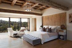 une chambre à coucher adulte avec deux fauteuils blancs et un plafond en bois
