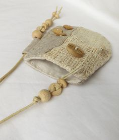 A beautiful patchwork talisman pouch, made using hand woven hemp, indian cotton and natural linen. It has hand stitched details around the edge and the button and beads are made from bamboo and wood. All natural materials :) Approximate size of the pouch is 11cm high, by 9cm wide. Ref: BTP105