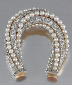 PEARL, TORTOISESHELL AND DIAMOND HAIR COMB, CIRCA 1915 Applied with a horseshoe shaped surmount of open work millegrain design, set with alternating lines of graduated pearls and circular- and rose-cut diamonds, to a two pronged comb of blonde tortoiseshell, later converted to a brooch, fitted case.