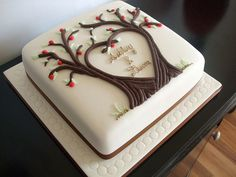Beautiful square cake with two trees whose branches form a heart. Couples names