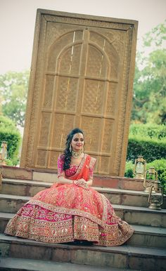 Pink and orange bridal lehenga, bride sitting on steps , one sided hairstyle , elbow length sleeves