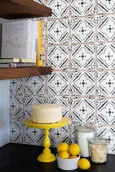 Black and white kitchen features a soapstone countertop and a white and black quatrefoil tile backsplash adjacent to a wall lined with stacked wooden floating shelves.