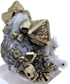 Pyrite crystals on a pyrite matrix covered with small quartz crystals - http://www.gemcoach.com/pyrite-guide/