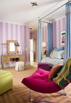 Wide-stripe walls featuring Ralph Lauren paint create an appropriately happy backdrop for the green and purple ottomans and fuchsia chair. The vertical striped walls and flowing canopy bed curtains add height to the ceiling, making the room appear larger