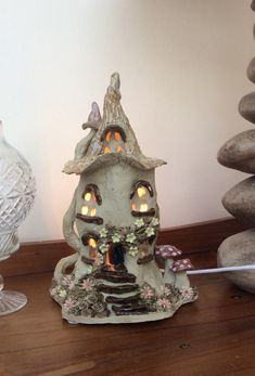 I made this fairy house electric lamp from stoneware clay and glazes then fired it in an electric kiln to 1,220 degrees centigrade. It is made entirely by hand without the use of a mould so each one is a little different. I cut out the windows and door so the light shines through to create a lovely warm glow. This particular lamp has a cream coloured roof, red and white spotted mushrooms, a chimney pot and log pile and little yellow and coral flowers. It is fitted with a 3 pin plug and a…