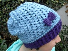 This trendy slouchy beanie hat is hand crocheted with a blend of light blue merino wool and acrylic yarn. It is super soft and warm. The special stitch used gives a very elegant texture. The beanie features a purple border and a pretty matching bow. The perfect Autumn/Winter fashion accessory! Slouchy Beanie, Beanie Hats, Hand Crochet, Crochet Hats, Autumn Winter Fashion, Fall Winter, Merino Wool, Light Blue, Bows