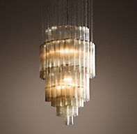 RH's Serenella Chandelier:In the style of Venini, our reproduction of a mid-century modern Murano design commands a room. Suspended from a cascade of metal chains, the magnificent 7-foot chandelier features concentric tiers of individually handblown tubular glass. Clusters of textured, smoky-taupe cylinders cast a warm, moody glow.