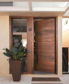 Entrada principal ganhou porta pivotante de angelim pedra e uma painel de vidro para a entrada de luz.. destaque tb para o vaso de planta
