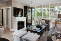 HGTV invites you to take a look at this transitional living room with a gray sofa and armchair set, striped hourglass ottomans and terrace access. Living Room Images, Living Spaces, Grey Armchair, Glass Front Cabinets, White Fireplace, Transitional Living Rooms, White Sofas, Single Doors, Sofa Set