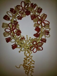 A wreath made of wire, red and gold beads.