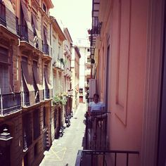 Travel writer, Ben Holbrook, writing notes on his apartment's picturesque Spanish balcony