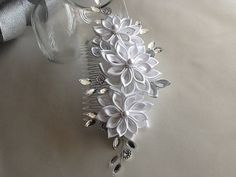 Hair Comb This stylish, elegant hair piece features pure white handmade Kanzashi flowers accented with pearls on silver bead caps on the centers. The flowers are made of pure white satin and the side petals in silver ribbon. The center flower measures 2.50 across and the side flowers