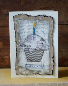 Original, handcrafted Birthday card has a cupcake design with the words Make A Wish at the bottom. It was collaged to vintage book paper and then