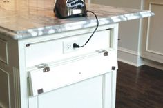 Rather than detracting from this handsome furniture-look island, the outlets are concealed behind a hinged drawer front that can be closed when the outlets are not in use.
