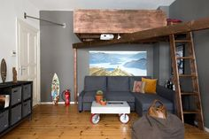 Great living room with grey walls and a wooden loft bed. Great industrial style!  See the whole makeover on our website!