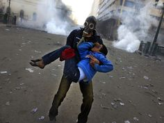 An Egyptian protester evacuates an injured boy during clashes near Tahrir Square in Cairo on Friday January 25, 2013