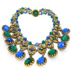 An exceptional piece of vintage costume jewellery. The necklace features beautiful faceted green and blue glass stones framed by filigree gold...