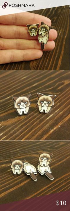 Grumpy Cat Cling Earrings Super cute Grumpy Cat Earrings.  Handmade by Nerdy But Still Girly.  Coated plastic charms and nickel free metal posts.  Rubber backings. Can wear them with just her face or you can put her tail end behind the ear to look like she is hanging from your ear. I am re-poshing these as I have a few other cat earrings that I like better. I have the card they came on as well. Makes a great gift! Nerdy But Still Girly Jewelry Earrings